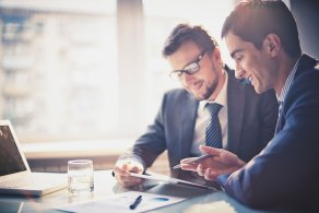 Image-of-two-young-businessmen-using-touchpad-at-meeting